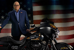 Bob Parsons next to a motorcycle and in front of an American flag